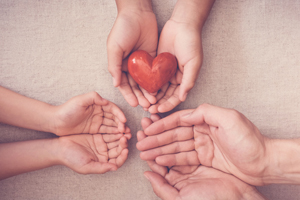 Photo illustration of hands holding a heart