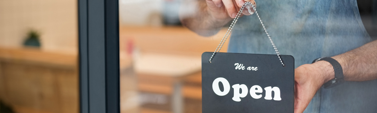 Small business owner hanging open sign