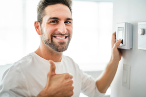 Man giving thumbs up while adjusting thermostat